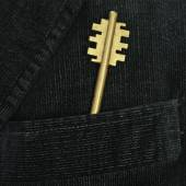 Golden metal key in a pocket of male suit — Stock Photo
