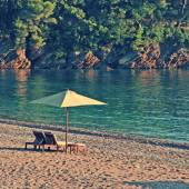 Two deck chairs and umbrella on the beach in rocky bay. — Stock Photo