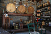 Wine barrels and bottles in the old cellar of a winery. — Stock Photo