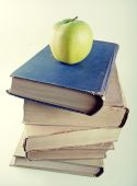 Stack of old hardcover books with green apple — Stock Photo