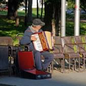 Accordion player sitting on bench in city park, Vienna, Austria. — Stock Photo