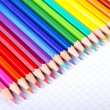 Multicolored crayons on white squared paper background. — Stock Photo #54455869