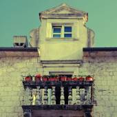 Balcony with flower pots in old european town — Stock Photo