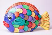 Multicolored ceramic fish on white background — Stock Photo