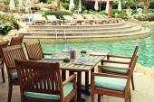 Table and chairs in outdoor cafe next to the resort swimming poo — Stock Photo