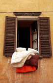 Old shutters window with bedclothes, Italy — Stock Photo