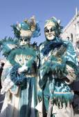 Masked persons in magnificent turquoise costume during the Carni — Stockfoto
