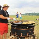 Man cooking crisp potato on the huge grill outdoor pan, Pirogovo, Kiev — Stock Photo #76329065