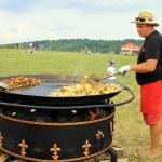 Man cooking crisp potato on the huge grill outdoor pan, Pirogovo, Kiev — Stock Photo #76329075