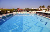 Hotel swimming pool with sun loungers — Stock Photo