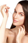 Beautiful model applying a cosmetic skin serum treatment — Stock Photo