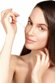 Beautiful model applying a cosmetic skin serum treatment — Stockfoto