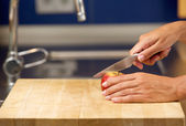 Female hands cutting apple on chopping board — Stock Photo