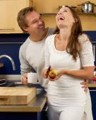 Happy couple laughing in the kitchen — Stok fotoğraf