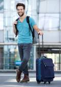 Young man waiting at airport with suitcase and bag — Stockfoto