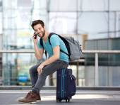 Young man sitting on suitcase and calling by cellphone — Stock Photo
