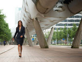 Young business woman walking on sidewalk — Stock Photo