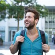 Happy young man listening to music on earphones — Stock Photo #52517781