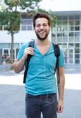 Young man standing with backpack and earphones — Stock Photo
