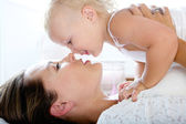 Attractive mother kissing cute baby girl — Stock Photo