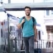 Happy young man walking with suitcase at train station — Stock Photo #53065337