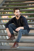 Cool guy in black clothing sitting on steps  — Stock Photo