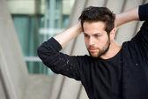 Stilig manliga mode modell poserar med händerna bakom huvudet — Stockfoto