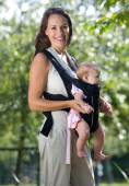 Beautiful mother with infant in sling — Stock Photo