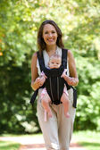 Happy mother walking with infant in baby carrier   — Stock Photo