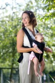 Cheerful mother with baby in sling — Stock Photo
