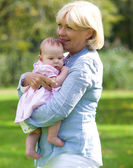 Grandmother smiling with baby granddaughter  — Foto Stock