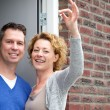 Happy couple holding keys to their new home — Stock Photo #53523849