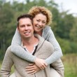 Smiling couple having fun with piggyback ride — Stock Photo #53737401