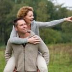 Happy man giving smiling woman piggyback ride — Stock Photo #53737413