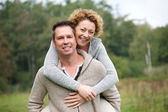 Smiling couple having fun with piggyback ride — Stock Photo
