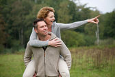 Happy man giving smiling woman piggyback ride — Stock Photo