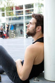 One man sitting outdoors on the floor in the city — Stock Photo