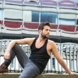 Male fashion model sitting outdoors in urban area — Stock Photo #53976839