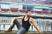Male fashion model sitting outdoors in urban area — Foto Stock