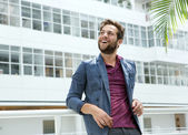 Smiling young man with beard standing in white building — Stock Photo