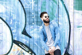Male fashion model with  sunglasses posing by graffiti  — Stok fotoğraf