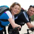 Happy couple smiling with their bikes — Stock Photo #54302413