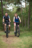 Happy couple cycling in nature — Stock Photo