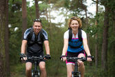 Man and woman cyclist smiling outdoors  — Stock Photo