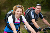 Smiling couple enjoying a bicycle ride outdoors — Stock Photo