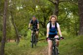 Happy couple riding bicycles outdoors — Stockfoto