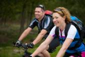 Cheerful couple enjoying a bike ride in nature — Stock Photo