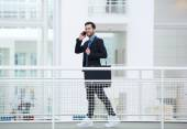 Businessman walking and talking on mobile phone — Stock Photo
