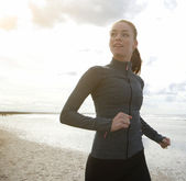 Female runner exercising by the beach — Stock Photo