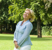 Middle aged woman smiling outdoors — Stock Photo